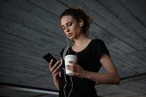 Woman holding coffee cup using mobile phone in basement
