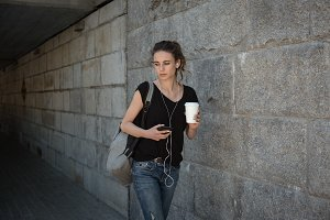 Woman holding coffee cup and listening to music on mobile phone in basement