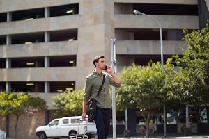 Man walking with suitcase while talking on mobile phone