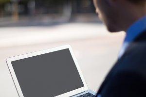 Businessman using laptop on street