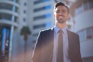 Smiling businessman standing near office building