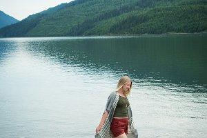 Young woman walking on log at lakeshore