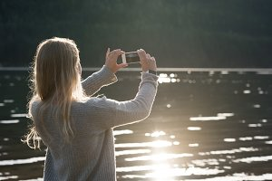 Rear view of woman photographing lake from mobile phone