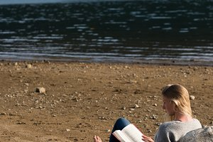 Rear view of woman sitting on sand reading novel