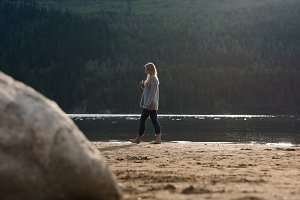 Side view of woman walking at lakeshore