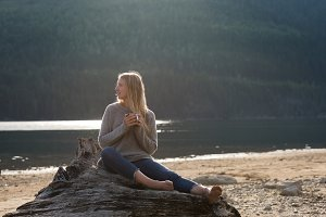 Blond woman sitting on log at lakeshore