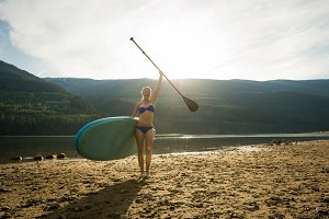 Portrait of smiling young woman standing with paddleboard and oar at lakeshore