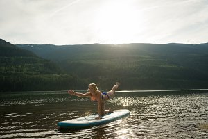 Woman practicing yoga on paddleboard in lake