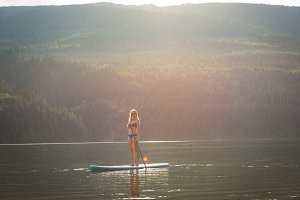 Young woman standing on paddleboard in lake