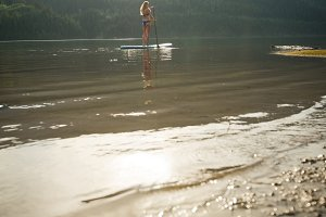 Distant view of young woman paddleboarding in lake