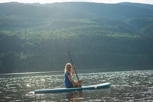 Side view of woman sitting on paddleboard in lake