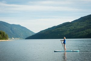 Side view of woman paddleboarding in lake