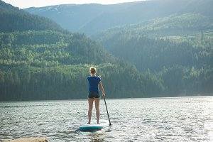 Rear view of woman paddleboarding in lake