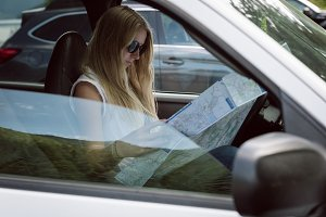 Side view of young woman looking at road map