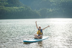 Excited young woman sitting on paddleboard in lake