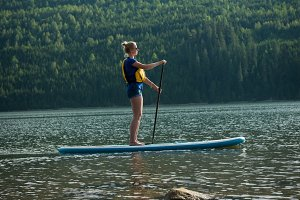 Side view of young Woman oaring paddleboard in lake