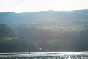 Distant view of woman paddleboarding in lake