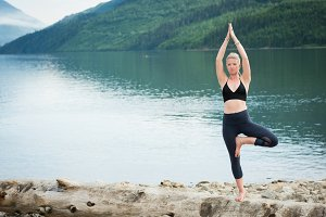Young woman practicing tree pose on log
