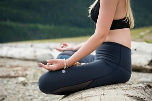 Low section of woman practicing lotus position