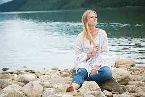 Beautiful woman sitting on rocks against lake
