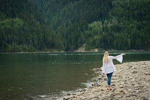 Rear view of young woman walking at lakeshore