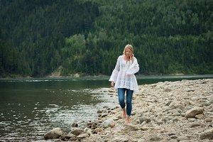 Young woman walking on rocks at lakeshore