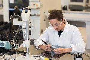 Female technician working on machine part