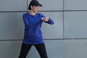 Woman checking time while performing stretching exercise outside building
