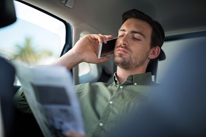Man talking on mobile phone while reading newspaper