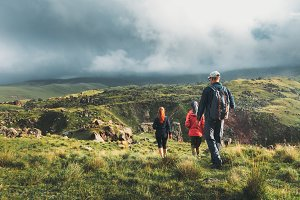 group of backpackers, a man and two women walking along the green hills against a background of clouds