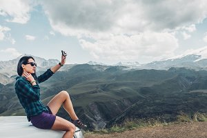 A beautiful young girl in a shirt and shorts sits on the hood of a car and makes selfie on the background of the summer mountains
