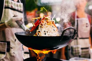Man cooks noodles on the fire