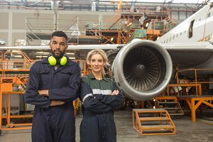 Aircraft maintenance engineers standing with arms crossed at airlines maintenance facility