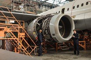 Aircraft maintenance engineers examining turbine engine of aircraft