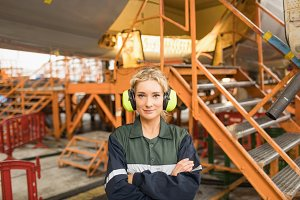 Male aircraft maintenance engineer standing with arms crossed at airlines maintenance facility