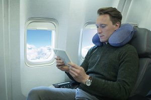 Male passenger using digital tablet in an aircraft