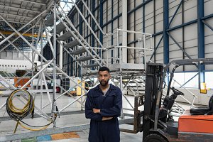 Aircraft maintenance engineer standing with arms crossed at airlines maintenance facility