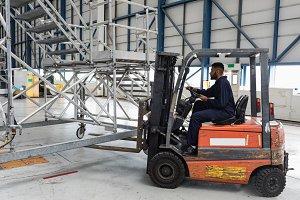 Aircraft maintenance engineer driving forklift truck