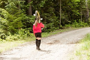 Rear view of woman carrying unicycle on dirt road
