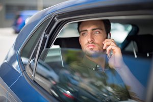 Man talking on mobile phone in car