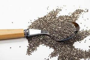 Spoon with chia seeds on white background. Healthy food.