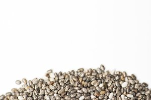 Chia seeds on white background. Isolated. Copy space. Vertical studio shoot.