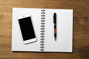 Smartphone with notebook and pen on wooden table. Office.