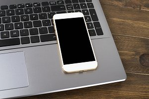 Smartphone next to laptop keyboard on wooden table. Office.