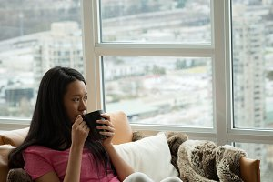 Woman having coffee while sitting on the couch