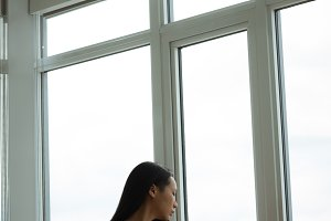 Woman looking through the window while holding coffee mug