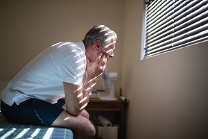 Side view of thoughtful senior male patient sitting on bed