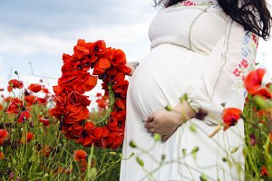 Pregnant woman on poppy field