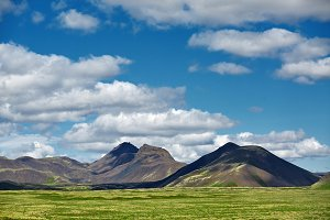 Beautiful Icelandic landscape with volcano, mountains, sky and clouds.