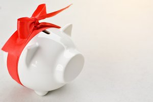 Piggy bank with red ribbon tape